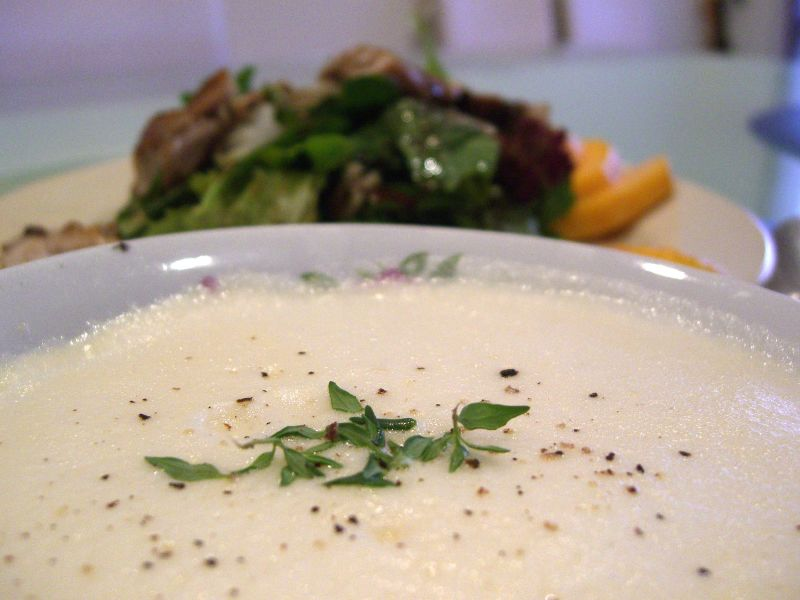 Avgolemono soup is garnished with fresh chopped herbs