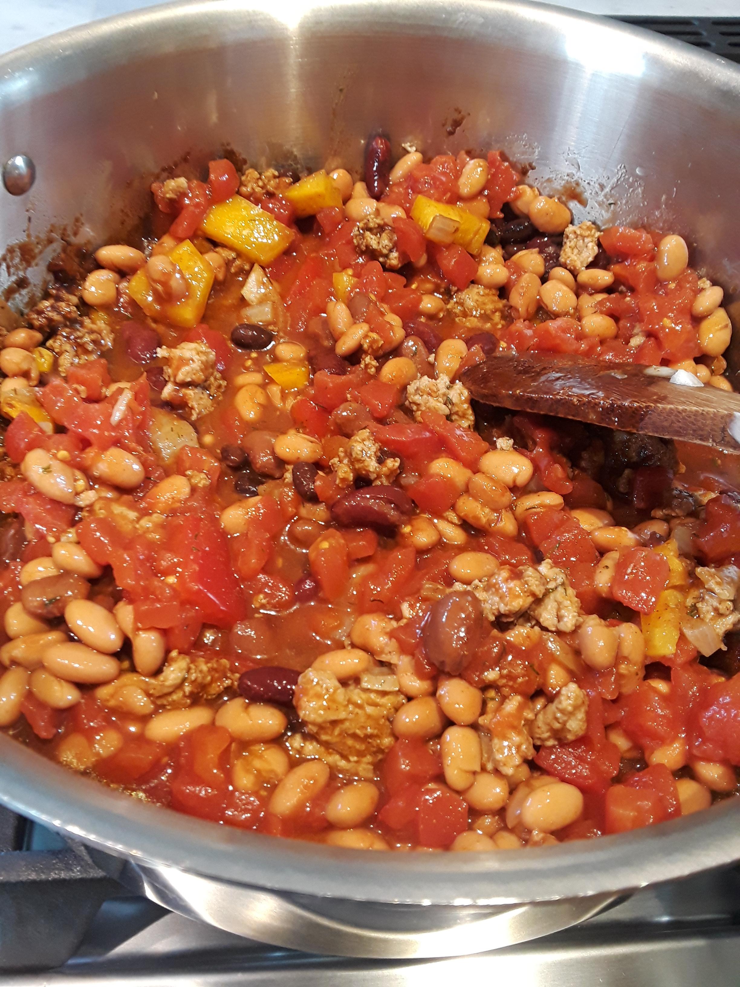 Adding veggies to chili