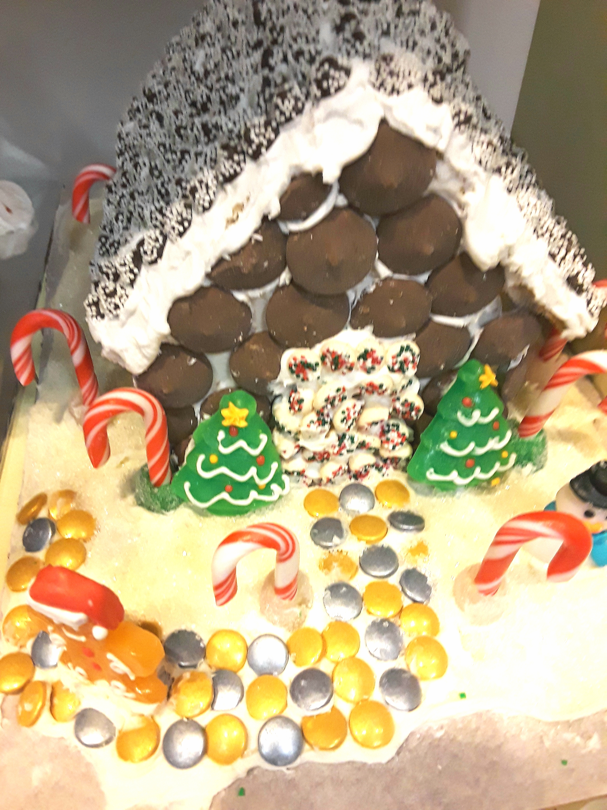 A gingerbread house is trimmed with snow caps, kisses, and candy canes