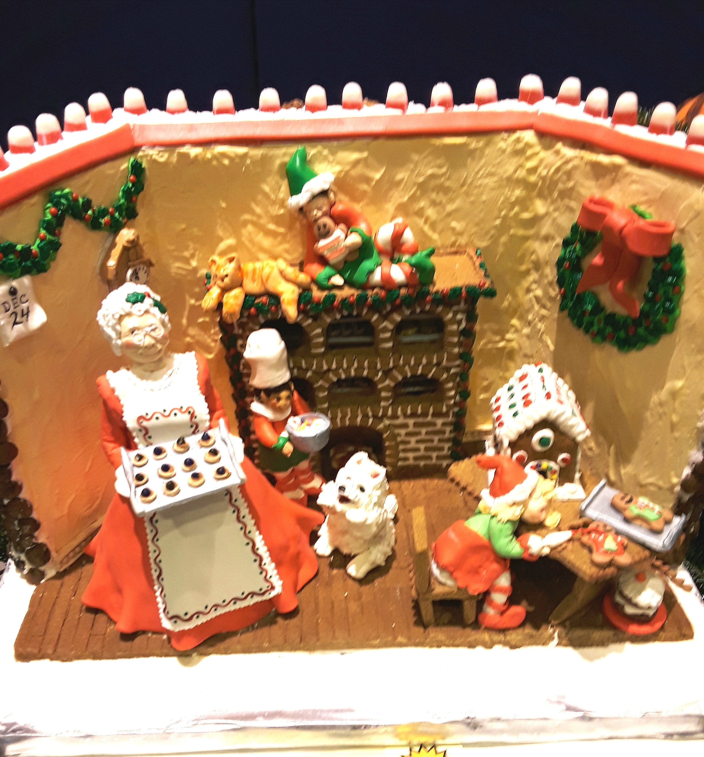 Gingerbread kitchen scene with cook and mini gingerbread house