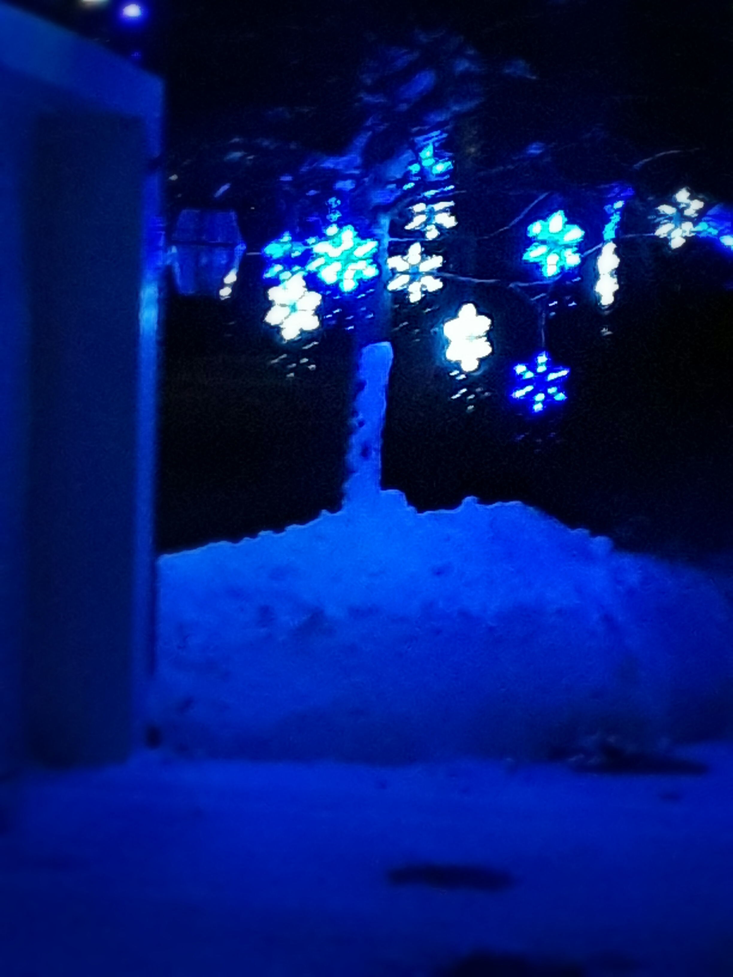 Snowflake holiday lights glow against a snowbank