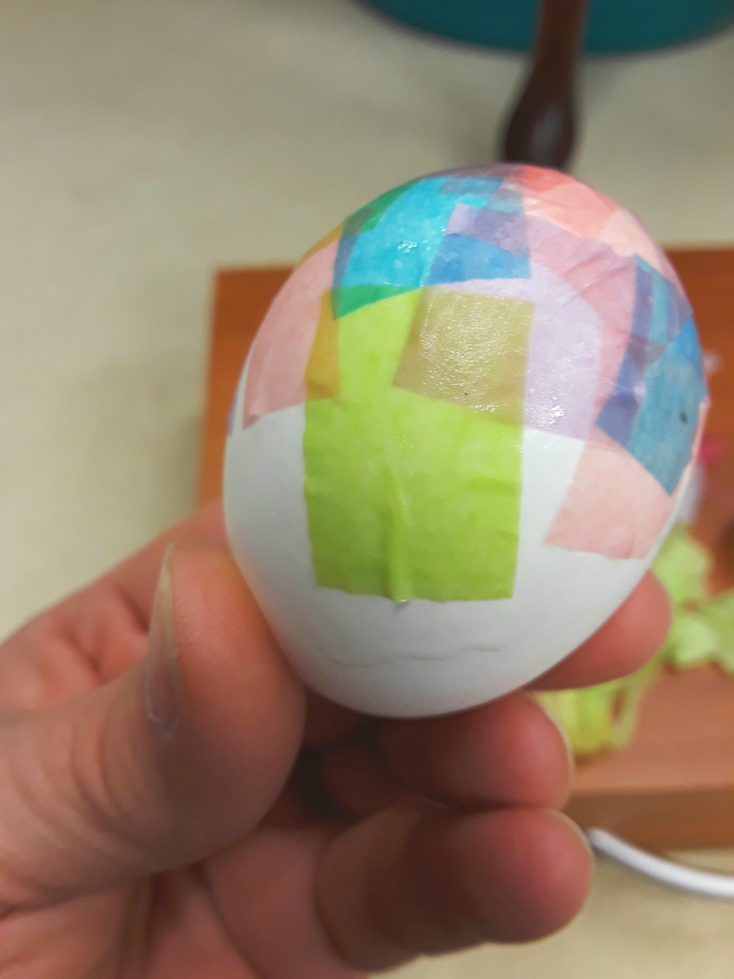 small squares of pink, green, and blue tissue are glued on to the egg