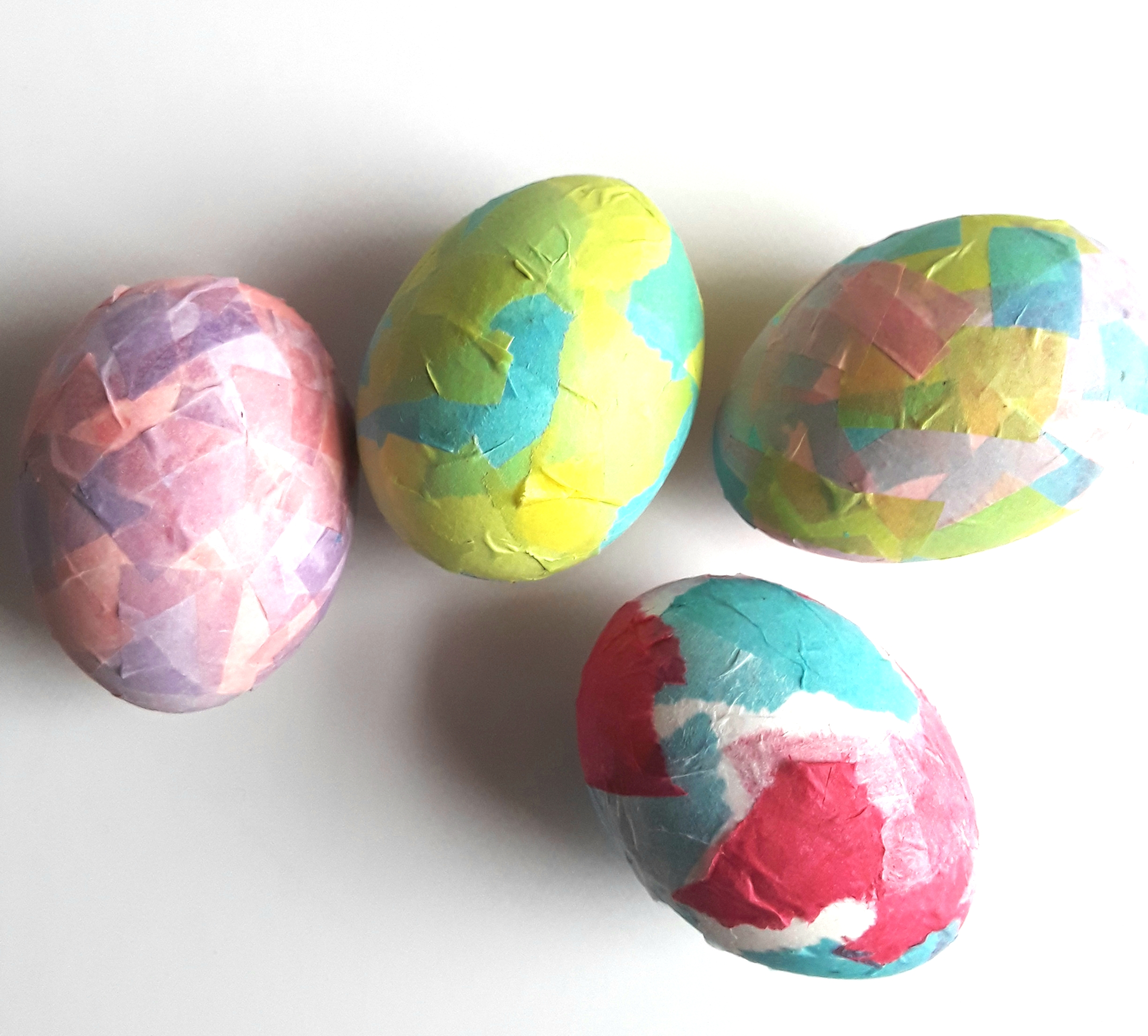 Pink, yellow, purple, and blue tissue paper squares overlap to create Easter Egg collages