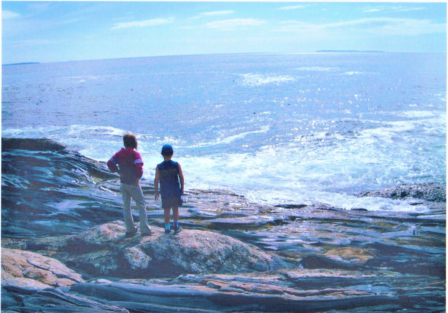 Sister and brother look out at the sparking blue ocean from atop a weathered rock.