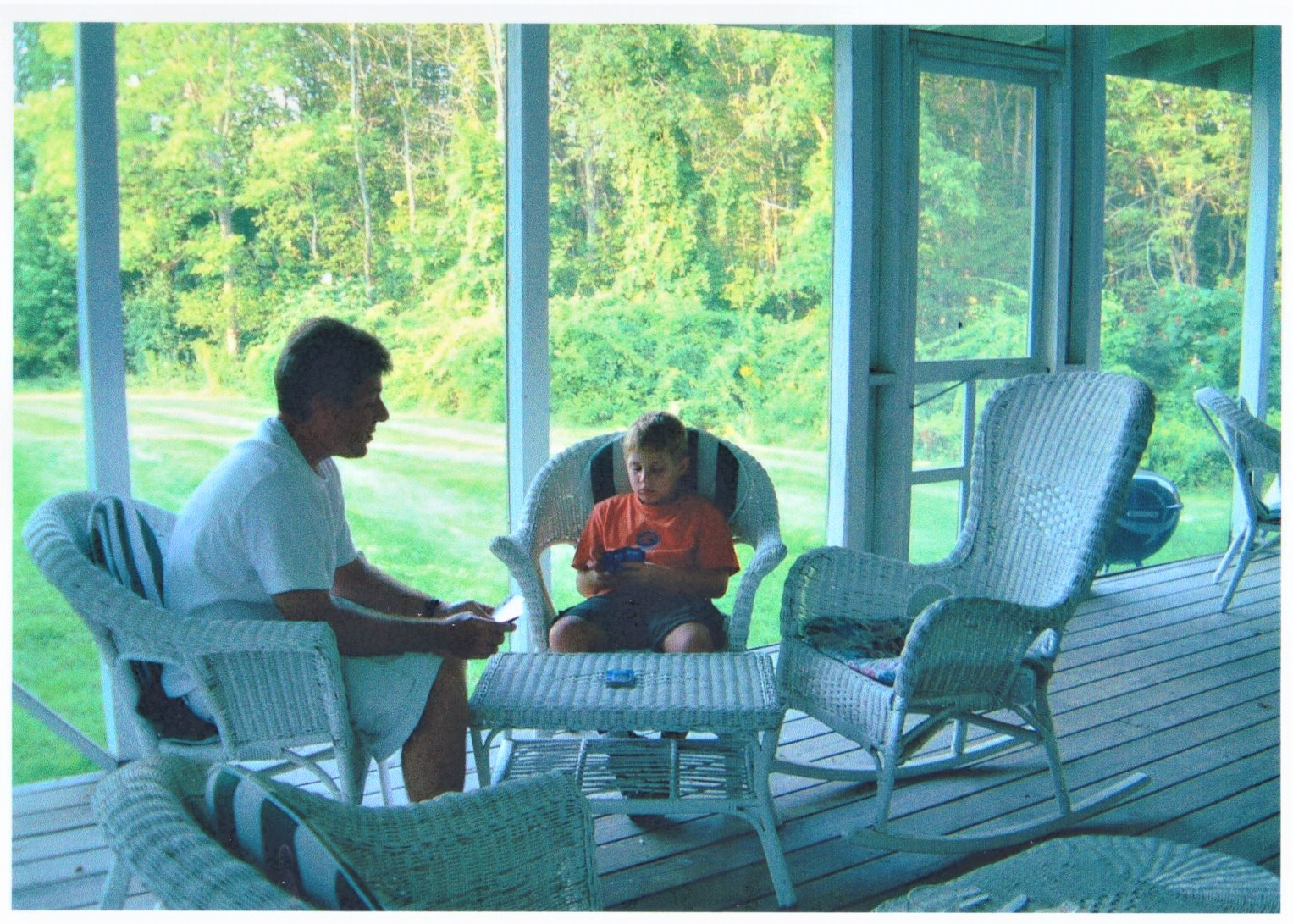 Father and son relax on wicker furniture in the hotel's screened back porch.