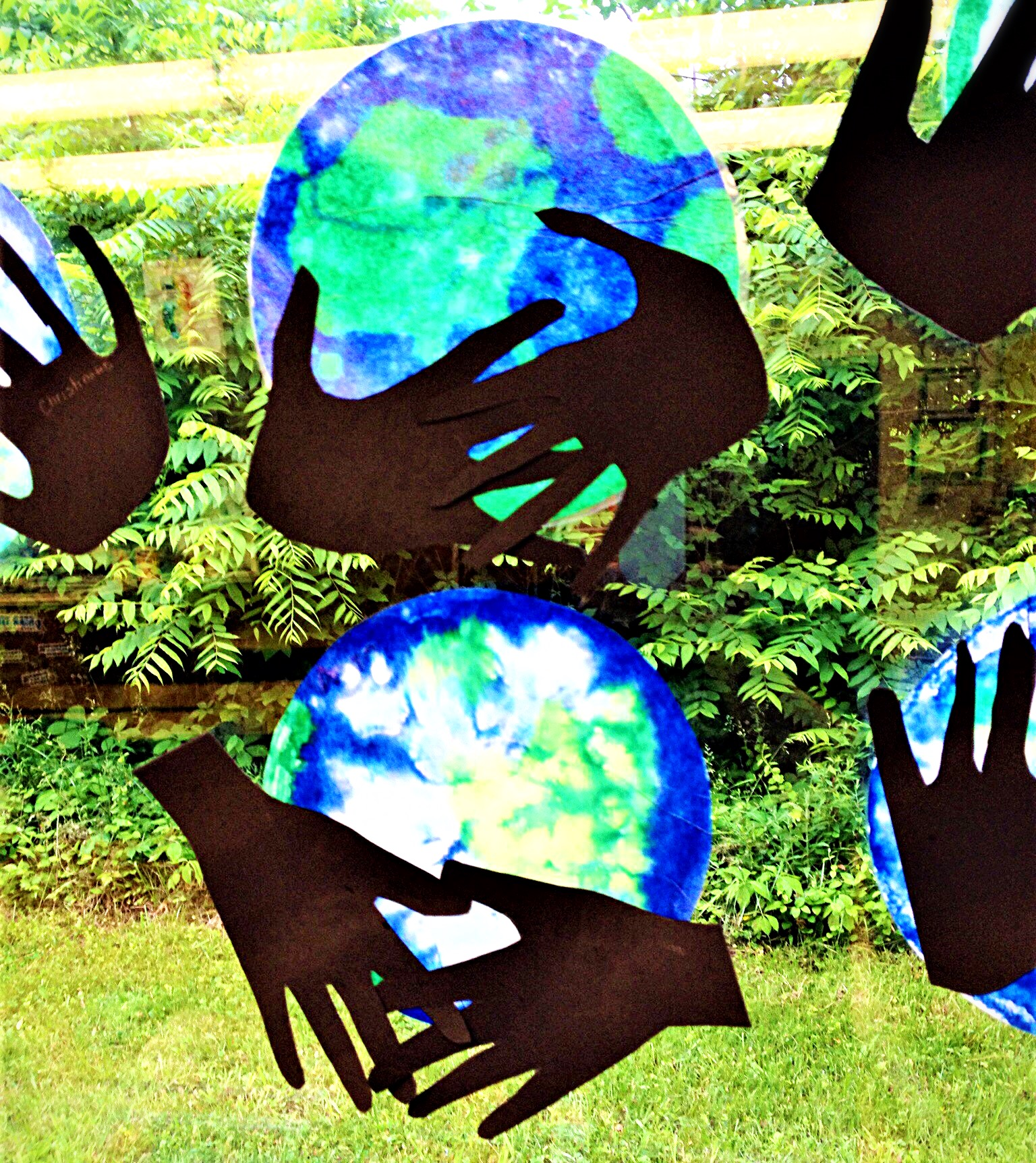 paper cutout hands hold a circle colored blue and green to resemble the Earth
