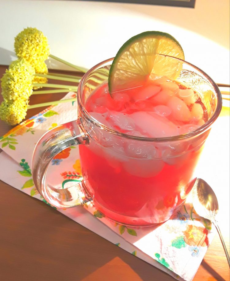 Mug of pomegranate fizz with lime slice