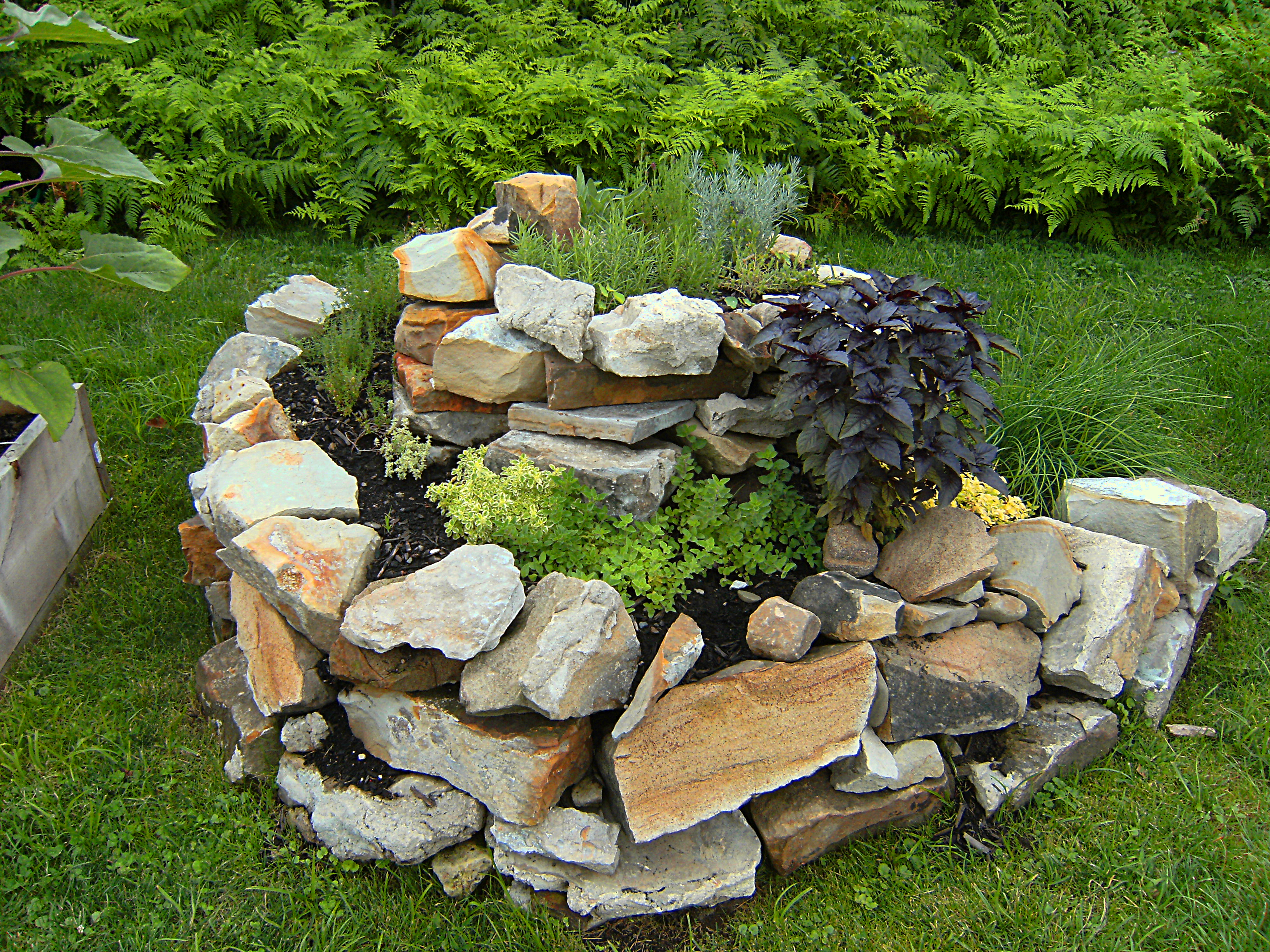 rocks are arranged in an open spiral and then filled with soil to make a planter