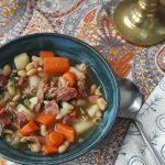 Ham and bean soup with chicken broth, carrots, potatoes, white beans, and arugula.
