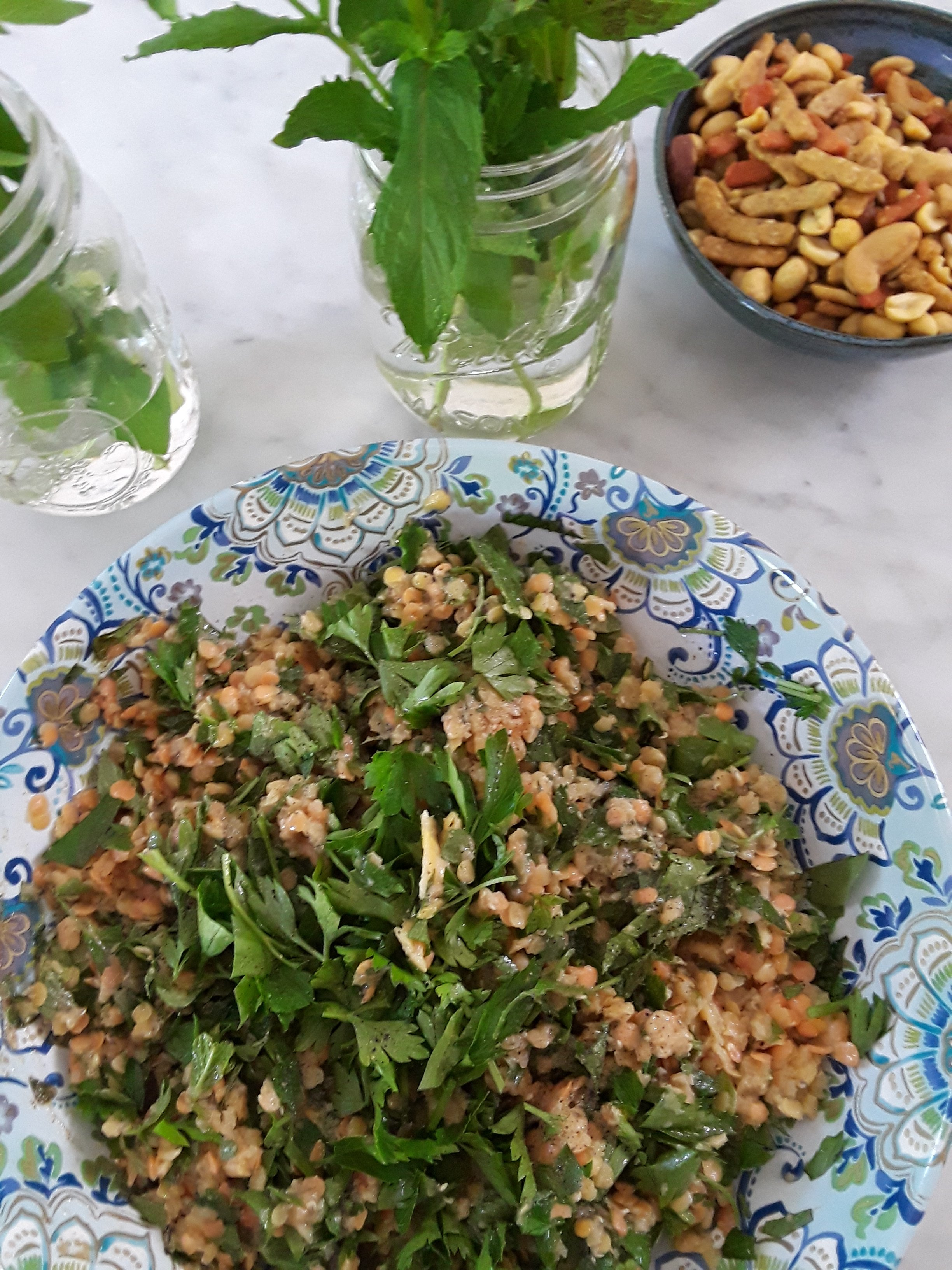 serving bowl with blue paisley pattern heaping with lentil salad made with herbs