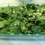 spinach mixture is spread over bottom half of phyllo dough layers