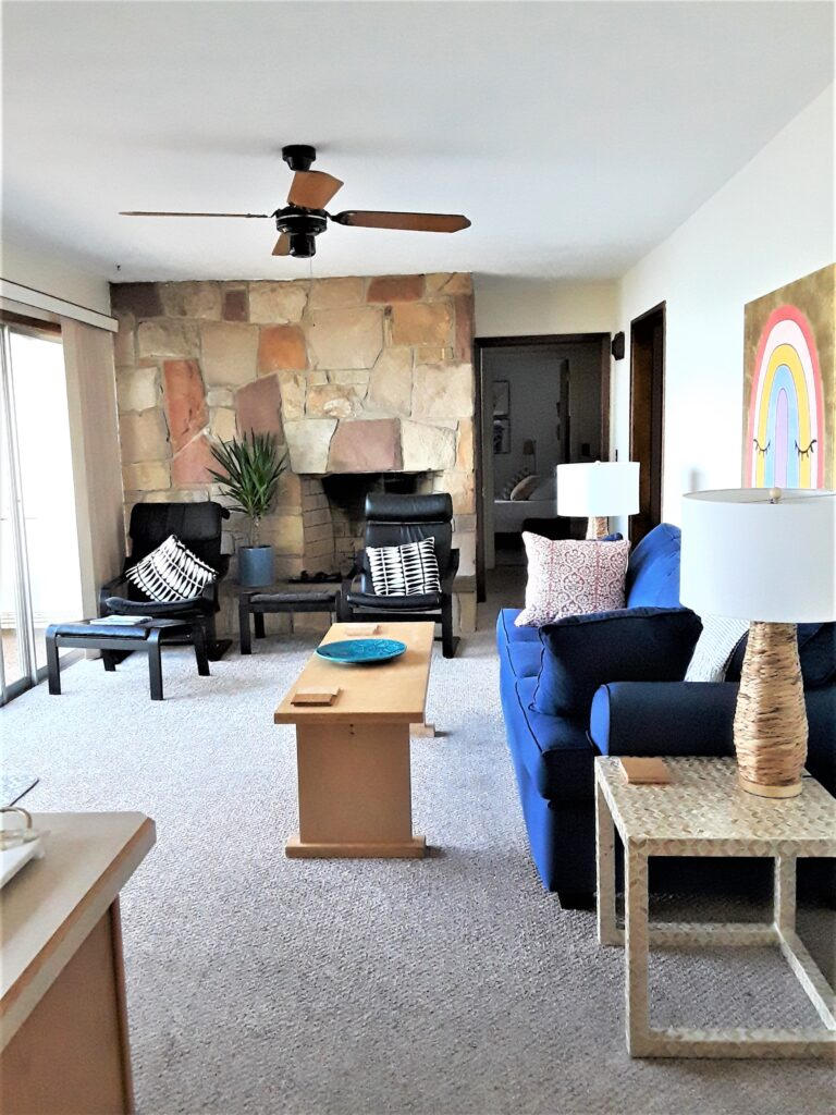An interior shot of the lake house shows a stone fireplace and blue couch.