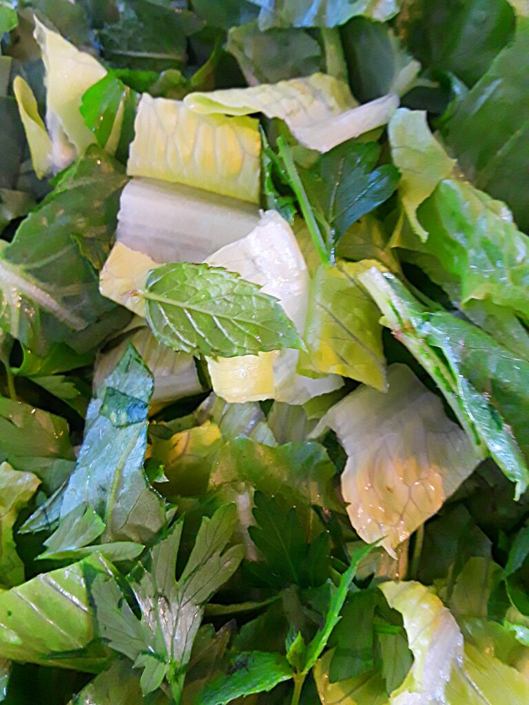 romaine lettuce is chopped and mixed with parsley and mint leaves.
