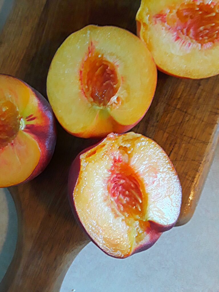Fresh peaches sliced in halves, stones removed.
