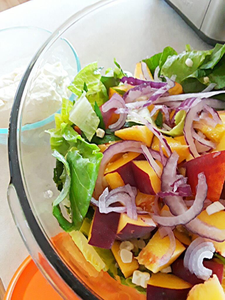 diced peaches, thinly sliced red onion, and greens in a salad bowl