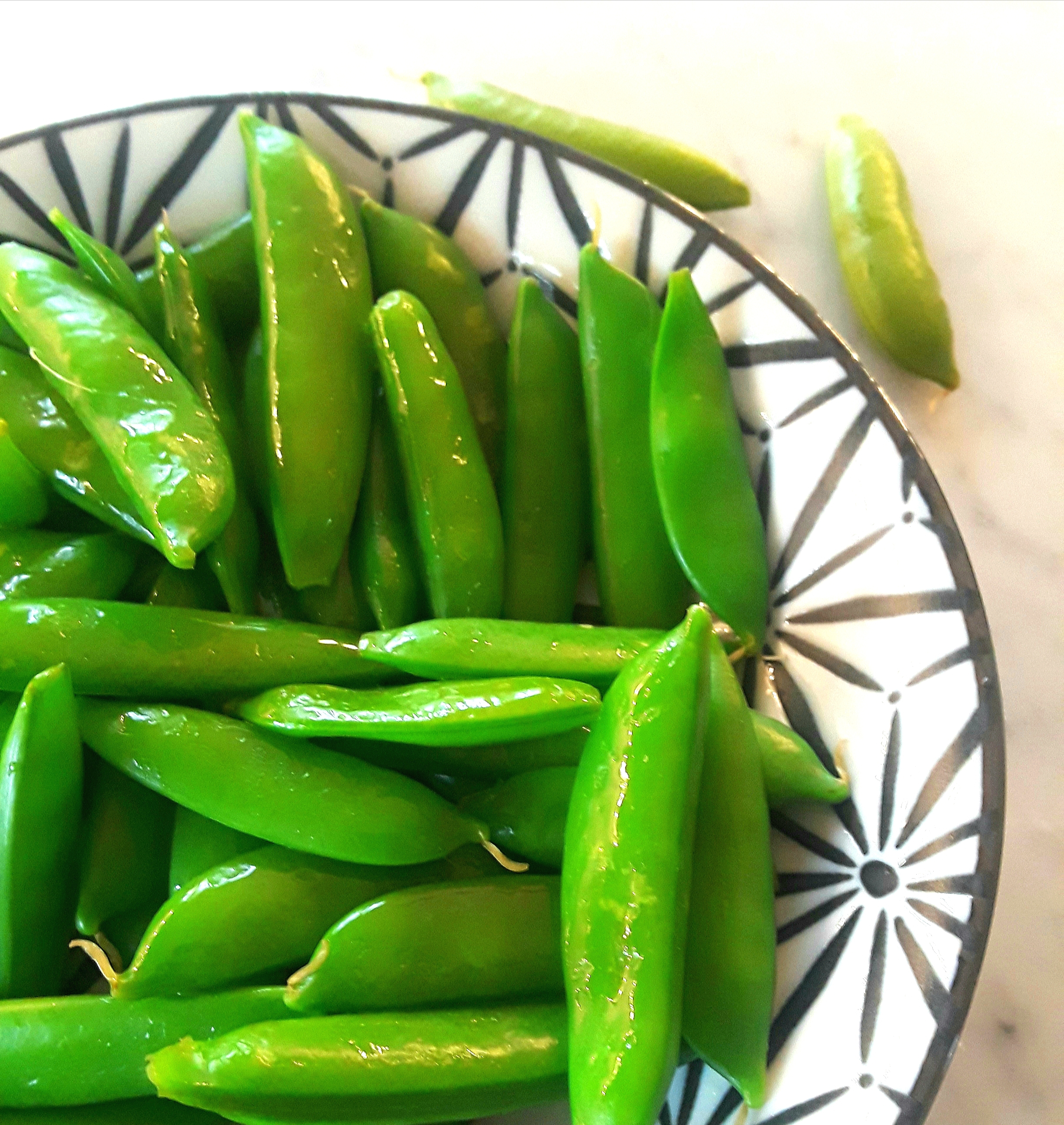 A bowl of vibrant, green, sugar snap peas is tasty.