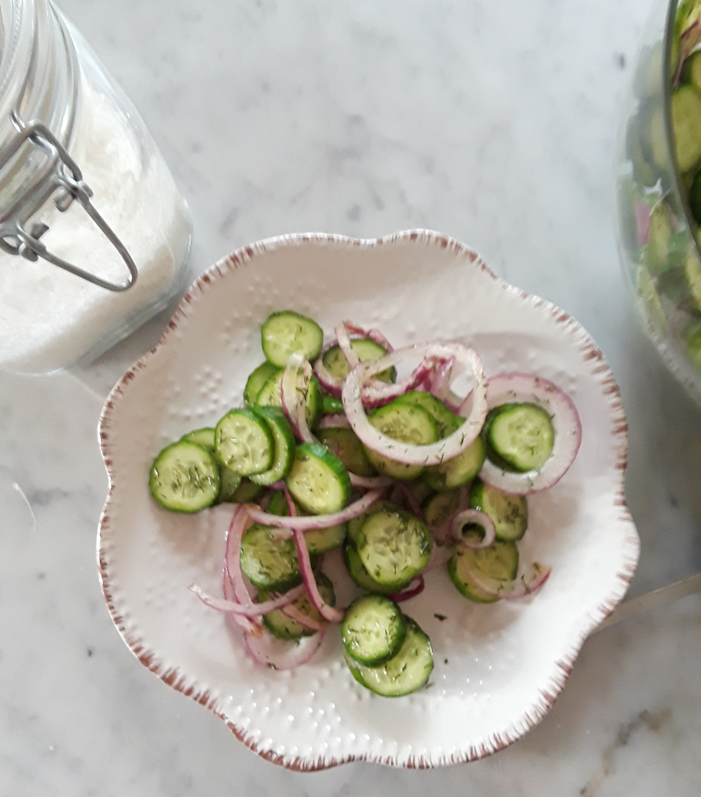 photo of sliced cucumbers and onions with spices and dressing